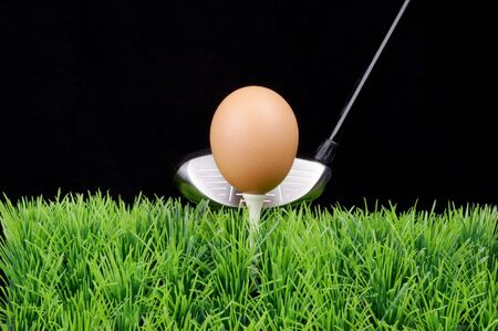 Single Easter Egg on a golf tee at the fairway, black background, Golf Driver behind photo