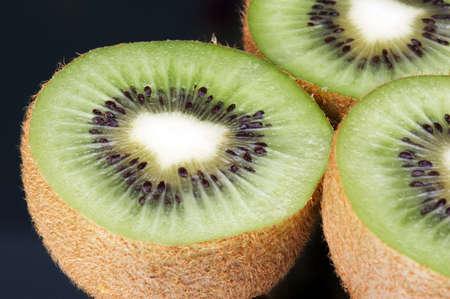 ingest: Kiwi fruit on black background - mirrage - landscape format Stock Photo