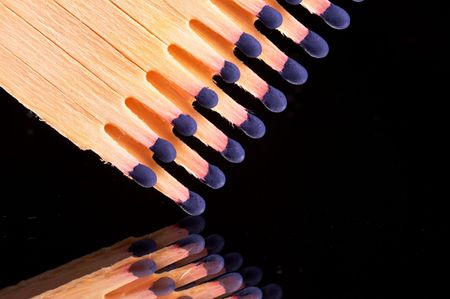 matches with blue match head in a row - landscape format - black background photo