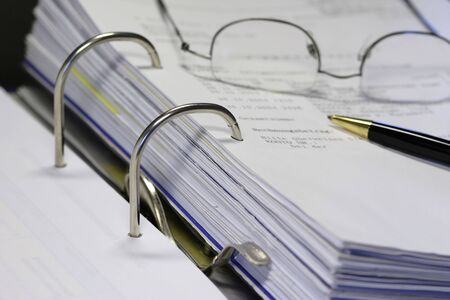 open binder with invoice and office items photo