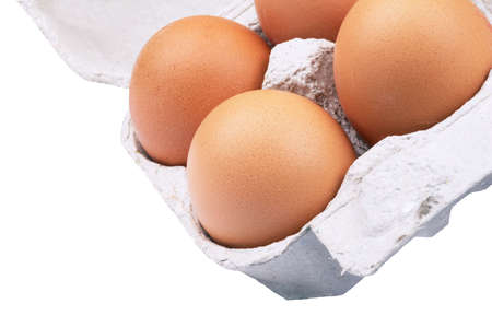 four brown eggs in a white box on white background photo