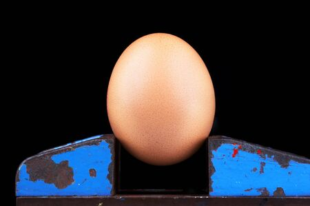 clamped: brownish egg made of felt clamped in a vice - on black background