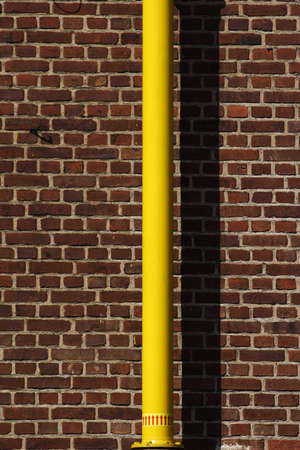 yellow pipe in front of a red brick wall, the yellow pipe is wet paint photo