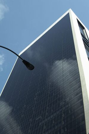 reflectivity: Facade of a modern office building - in the front the clouds are reflected