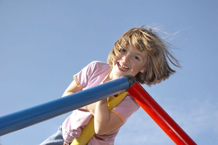 young girl playing on a climbing pole - looking down to the photografer