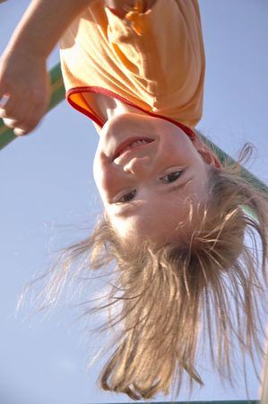 child on climbing pole - head first and laughing Stock Photo