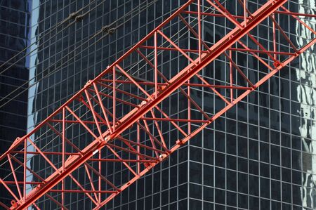 reflectivity: red construktion cran in front of black blend office building