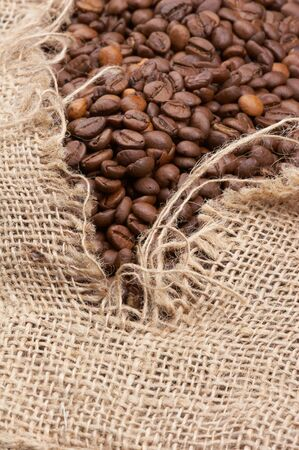 brown coffe breans in a tattered burlap sack Stock Photo