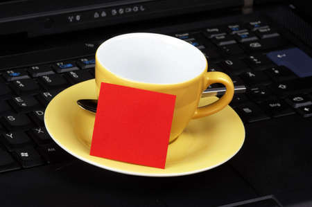 yellow cup with red post-it on black laptop photo