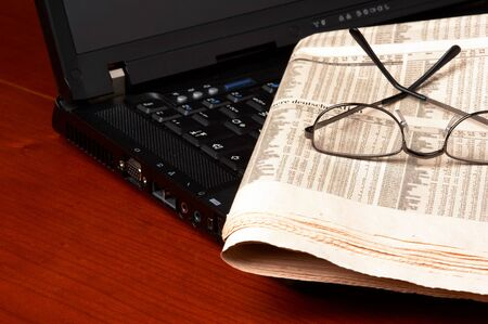 Desk with laptop, newspaper, glasses photo