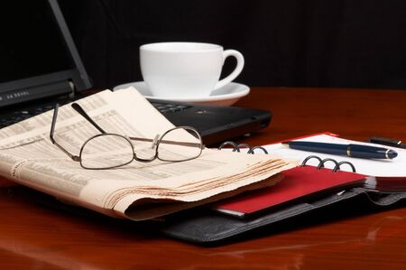 Desk with laptop, ring binder, newspaper, glasses and a cup of coffee photo