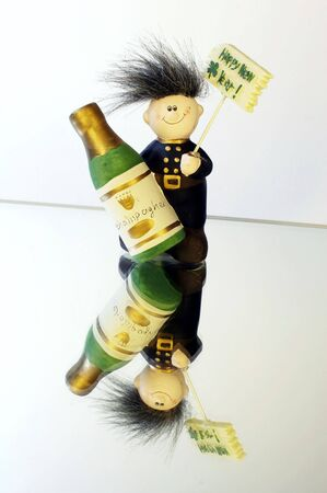 hogmanay: chimney sweeper on a mirror with Happy New Year sign and Champagne bottle in his hand Stock Photo