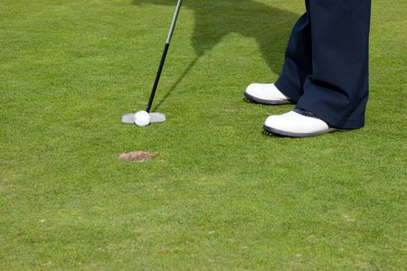 On the Putting green with putter in action photo