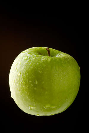 ingest: Green Apple with waterdrops on black background
