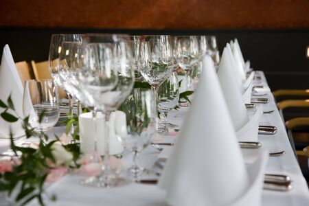 Well-laid table with white folded serviettes and wine glasses. Stock Photo