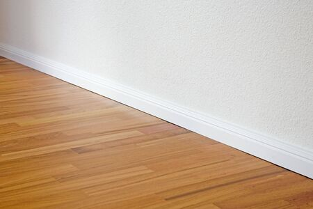 Doussie parquet floor with reddish surface and white walls