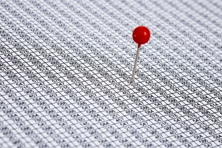Round red pin on a desert of numbers photo