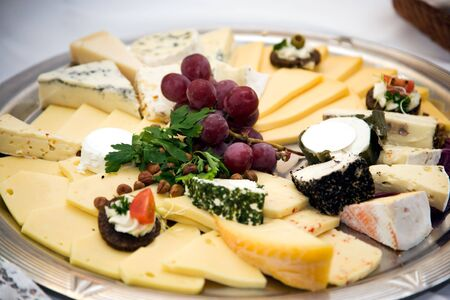 queso de cabra: Tabla de quesos con racimo de uvas