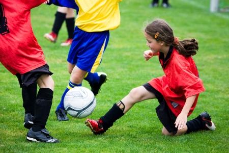 jugando al futbol: Ni�a jugando al f�tbol