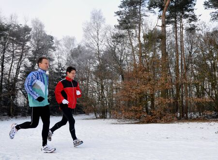 Mother and son running in the snow photo