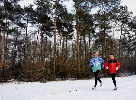 Runners in the snow in winter photo