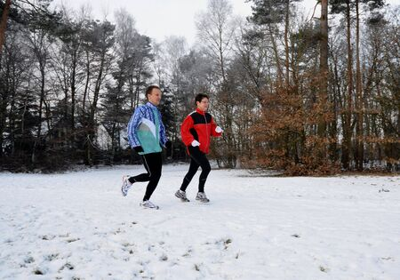 Healthy people running in the winter snow photo