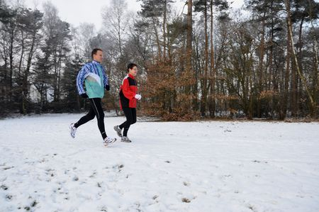 Two sporty people running in the wintersnow photo