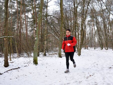 herself: Senior woman keeping herself fit by running in the snow Stock Photo