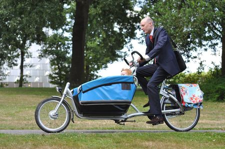 Business men hurrying on the carriere bike to the child´s creche Stock Photo