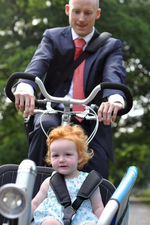 Business men riding his young child to the creche