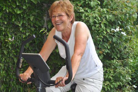 Laughing senior exercising on her hometrainer Stock Photo