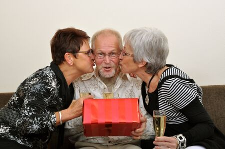 Senior man spoiled by presents and kisses