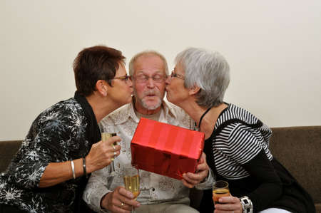 Senior man overwhelmed by the attention of two ladies photo
