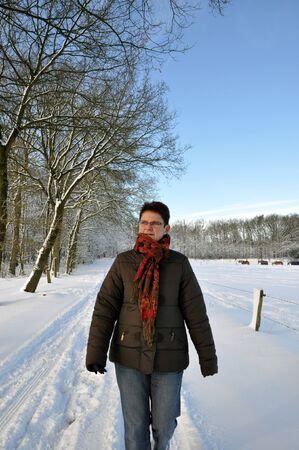 keeping fit: Senior keeping fit in winter time by walking in the snow