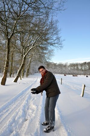 Senior keeping fit by throwing snowballs photo