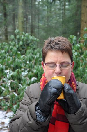 Senior woman keeping her hands warm with a hot drink photo
