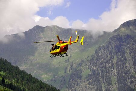 Rescue helicopter in the mountains lifting up