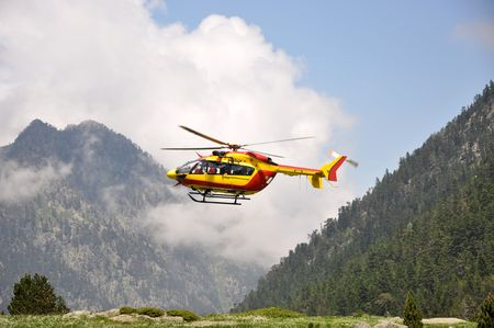 Red and yellow rescue helicopter in the mountains