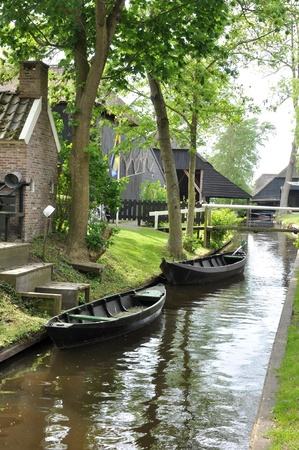Small canals with two ancient boats in the Netherlands