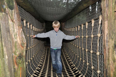 Young boy crossing a hanging rope bridge