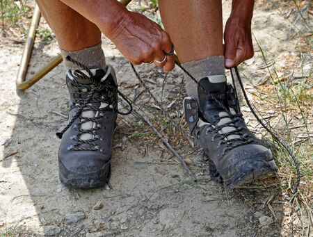 Strapping the walkingshoes before a long hike Stock Photo
