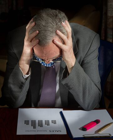 Manager at desk trying to cope with problems caused by corona virus
