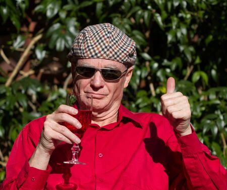 Older man giving thumbs up to wine and sunshine wearing sunglasses sunglasses