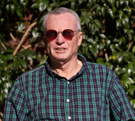 Older man in bright sunlight wearing sunglasses