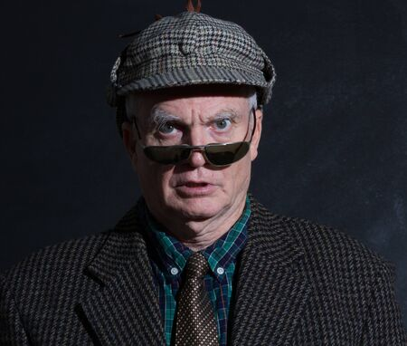 Grumpy English gentleman in tweeds, deerstalker and sunglasses