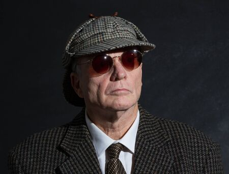 Elderly eccentric English gentleman in Harris Tweed and deerstalker and sunglasses
