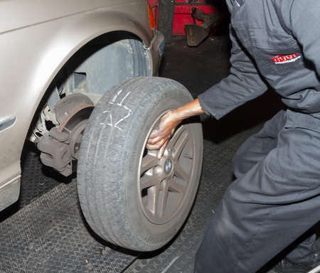 Checking spare tyre in boot of BMW at workshop