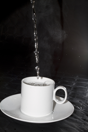 pouring hot water in white cup