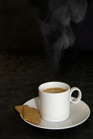 hot damping coffee in white cup with cookies