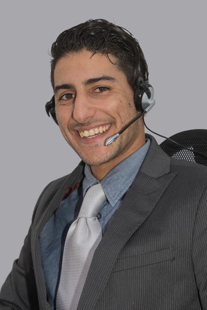 accommodating: A friendly young man on an office chair having a conversation with a customer or prospect using a head set